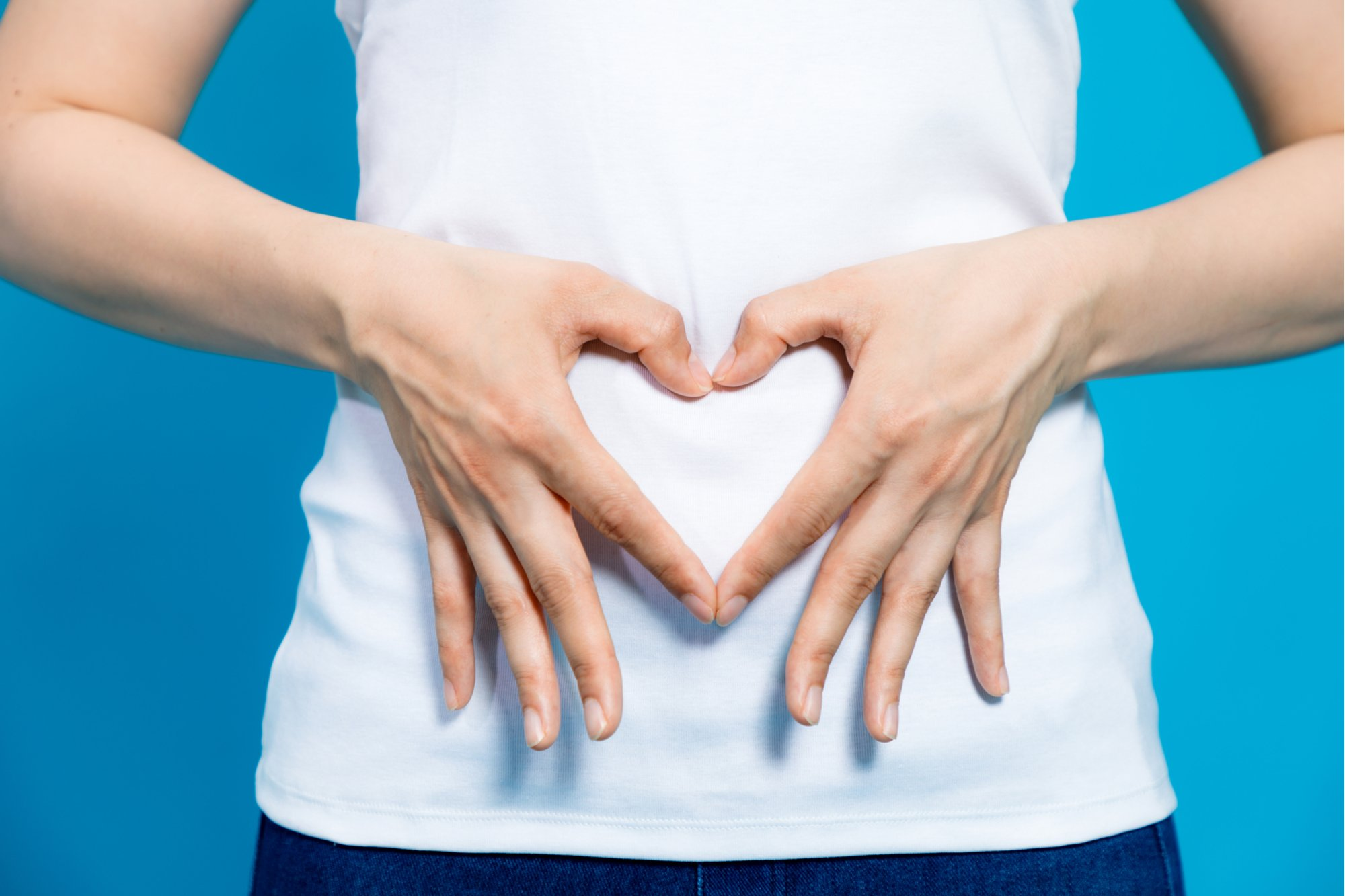 Female heart shaped hands on belly showing a healthy digestive system