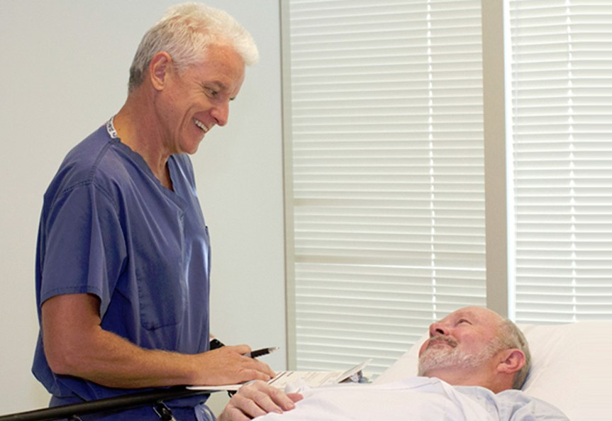 Happy physician reassuring a patient after his endoscopy procedure and telling patient about post endoscopy prep