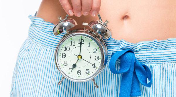 Alarm clock at abdominal level in female hands closeup